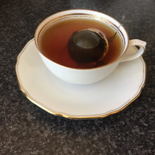 tea and tea ball in white cup